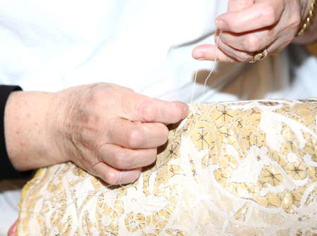 needle lace: hands of the elderly while embroidering a lace with lace pillow near venice in italy