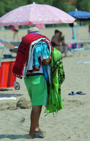 clandestine: african peddler of sheets and towels on the beach