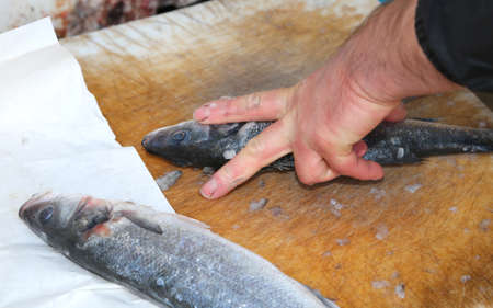 fishmonger: hands the fishmonger at the seafood market during cleaning of freshly caught fish