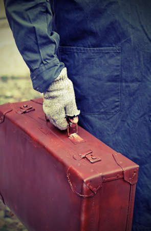 poor immigrant with old leather suitcase and the unstitched glove while traveling overseas jobs
