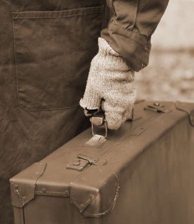 marginalized: immigrant with old leather suitcase and the broken glove while traveling overseas jobs Stock Photo