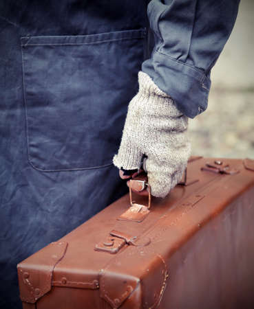 poorness: emigrated with old leather suitcase and the broken glove during travel abroad