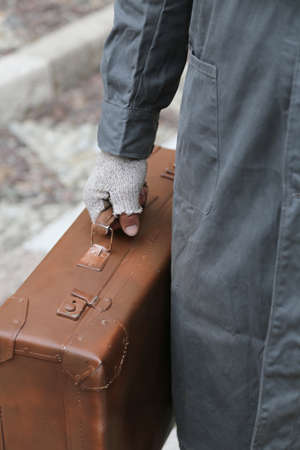 seniority: poor immigrant with old leather suitcase and broken gloves during the trip abroad in winter Stock Photo