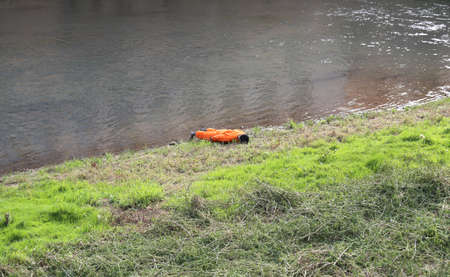 simulate: dummy  with orange jumpsuit on the river bank during a training exercise of civil protection