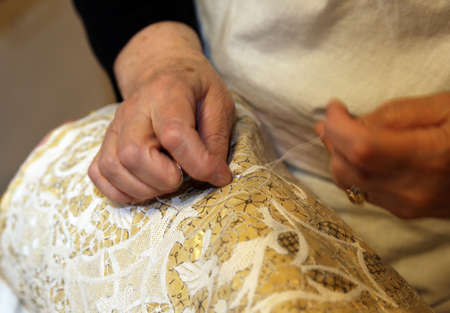 trabajo manual: elderly while embroidering a lace with lace pillow in burano island near venice Italy Foto de archivo