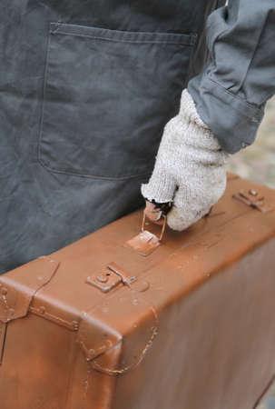 hombre pobre: pobre hombre con la vieja maleta de cuero y guantes rotos durante el viaje