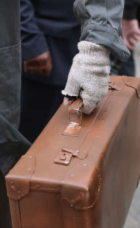 poor migrant with old leather suitcase and the broken glove during travel abroad