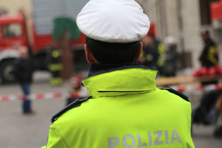 roadblock: italian chief of police with uniform phosphorescent and white hat during the traffic control written POLIZIA  which means POLICE in Italian Stock Photo