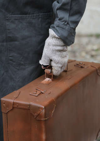 duffel: poor immigrant with leather suitcase and broken gloves during the trip abroad Stock Photo