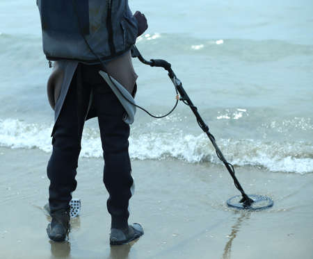 technologically: Man with metal detector on the beach to find lost objects under the sand of the ocean Stock Photo
