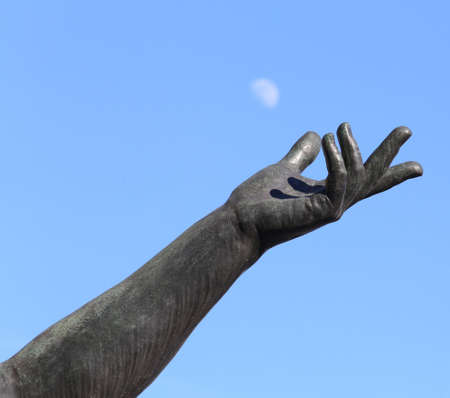 hand of statue trying to catch the white moon in the blue sky Stock Photo