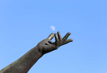 hand of statue trying to catch the white moon