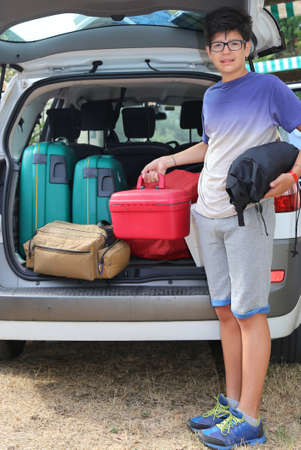 duffel: cute boy with glasses loaded the trunk of the car before leaving with family