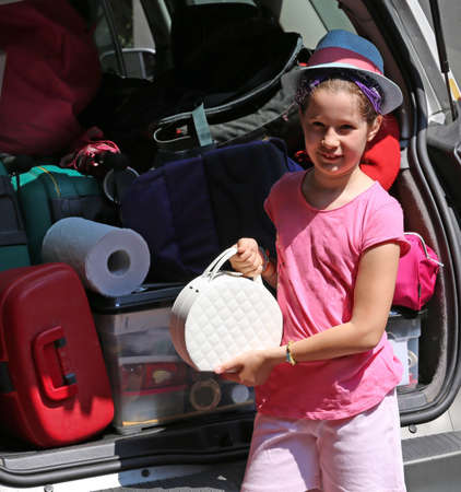 duffel: beautiful little girl with fashion Hat loads the trunk of the car before departure