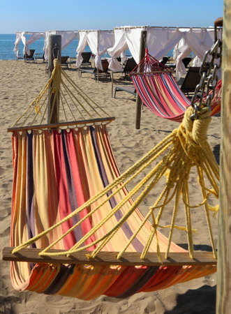 repose: Hammock on the beach of the tourist resort for relaxation of people during the summer holidays
