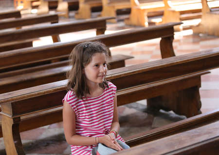 pretty little girl on Pew in the church during a prayer Stock Photo