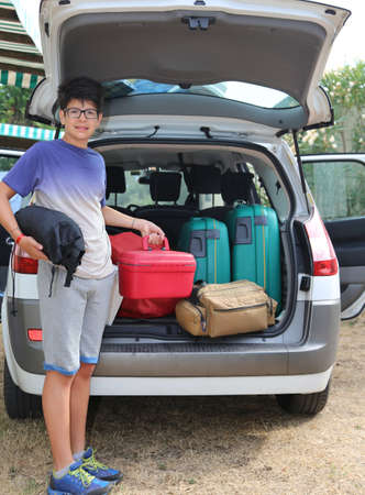return trip: young boy with glasses loaded the trunk of the car before departure