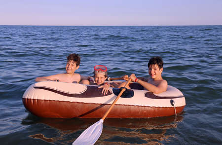 three children on the inflatable dinghy at sea in summer