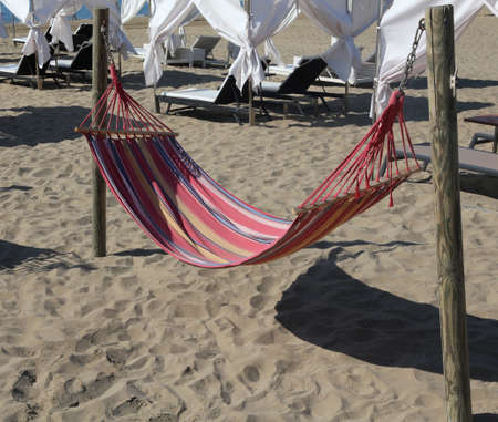 repose: Hammock on the beach of the tourist resort for relaxation of tourists