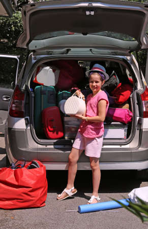 duffel: nice little girl with fashion Hat loads the trunk of the car before departure