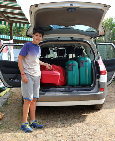 duffel: boy helps load the trunk of the car before leaving for a long journey Stock Photo