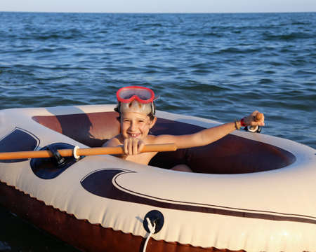 diving mask: smiling little girl with the diving mask on the inflatable dinghy Stock Photo