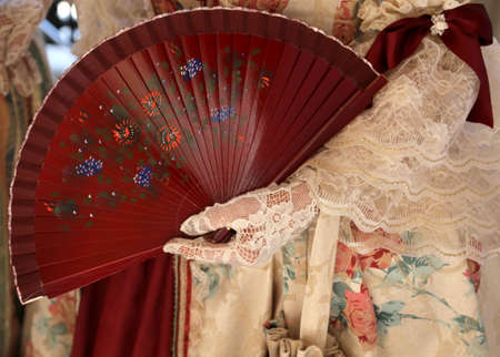 elegant woman with an ancient ceremonial dress and the fan in her hand with white glove