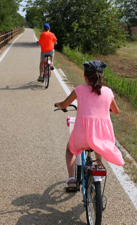 two little boys are riding on the bike path near the lagoon of Venice in summer