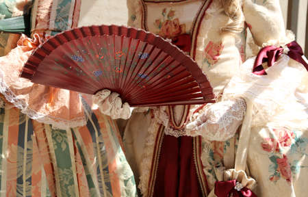 elegant woman with an ancient ceremonial dress and the fan  with white glove