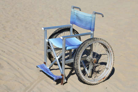 dystrophy: isolated wheelchair made of aluminum with special wheels on thesand Stock Photo