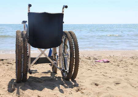 differently: wheelchair on the beach by the sea in summer