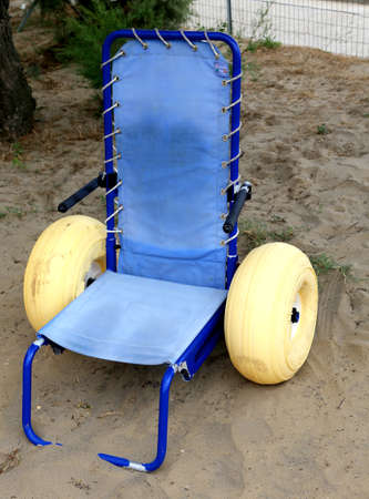 dystrophy: Special wheelchair with inflatable tires go on the sea Stock Photo