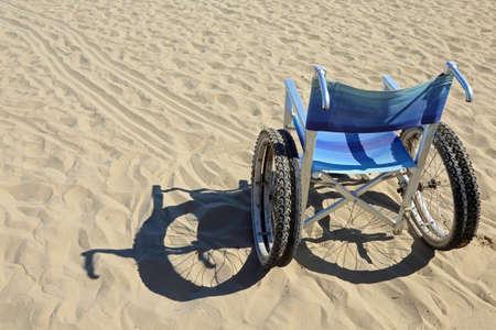 als: aluminum wheelchair on the sand of the beach Stock Photo