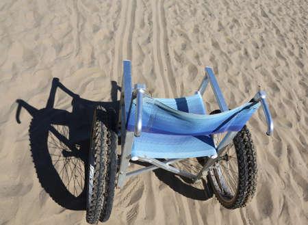 paraplegia: aluminum wheelchair on the sand of the beach Stock Photo