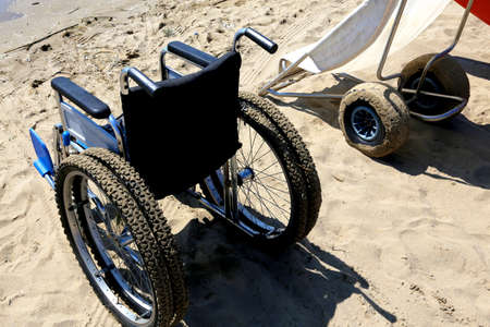 dystrophy: two special wheelchairs on the sand of the beach to the sea Stock Photo