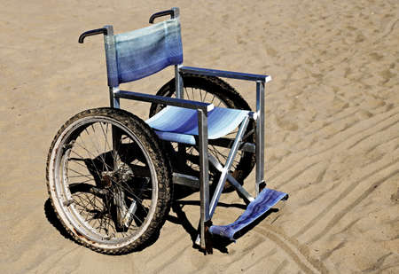 dystrophy: wheelchair on the sand of the beach in summer