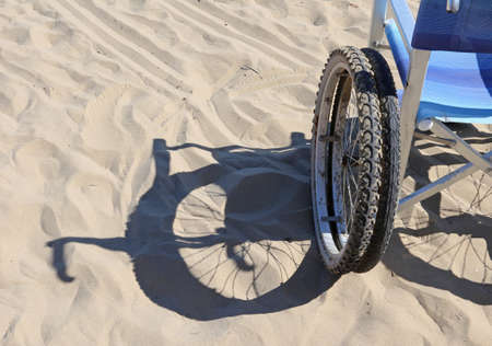 dystrophy: shadow of a wheelchair on the sand