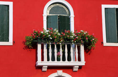 balcony window: beautiful flowered balcony with a window in the house and many flower pots