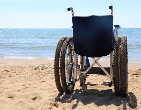 dystrophy: big wheelchair on the sand of the beach in summer Stock Photo