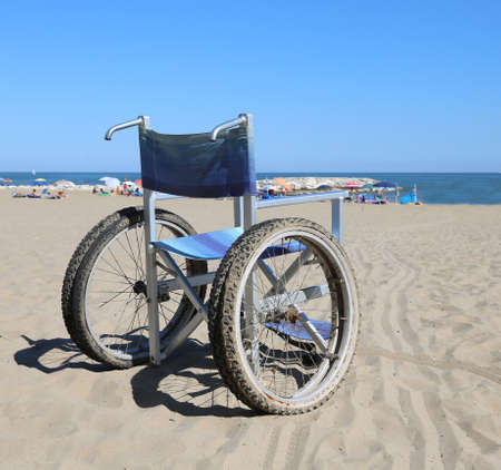 Modern wheelchair on the sand beach near the sea with many umbrellas Stock Photo