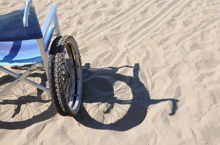 dystrophy: shadow of a wheelchair on the beach sand