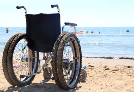 dystrophy: wheelchair aluminum on the sand of the beach to the sea