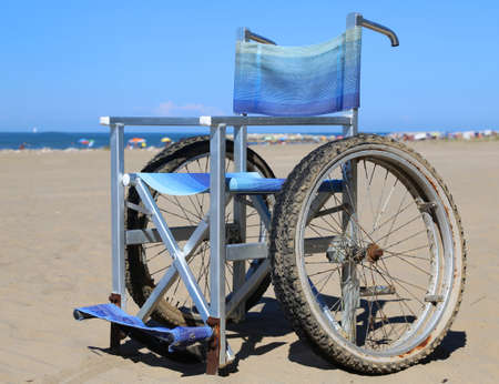 Modern wheelchair in aluminum with special wheels to move on the beach sand
