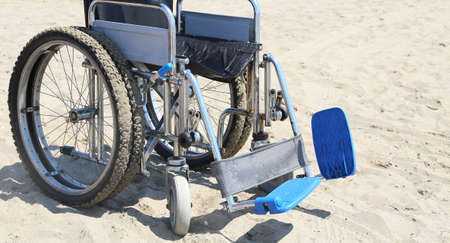 disablement: Wheelchair on the hot sandy beach in summer