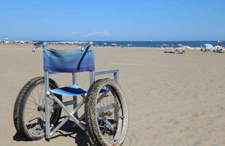dystrophy: wheelchair aluminum on the sand of the beach in summer