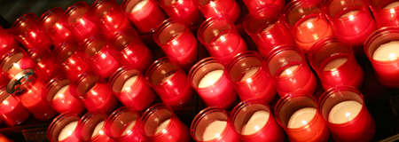 liturgical: many candles lit with flickering flame in the place of prayer Stock Photo