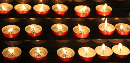 many candles lit inside the place of worship to pray