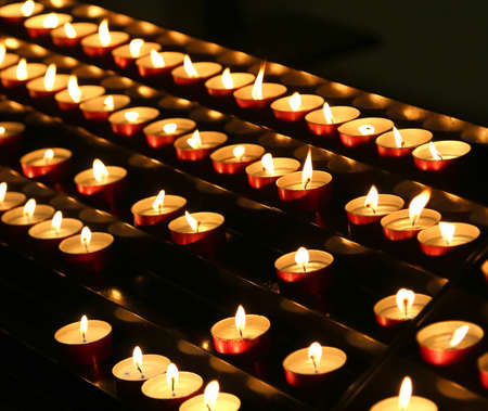 series of candles lit with flickering flame in the place of prayer