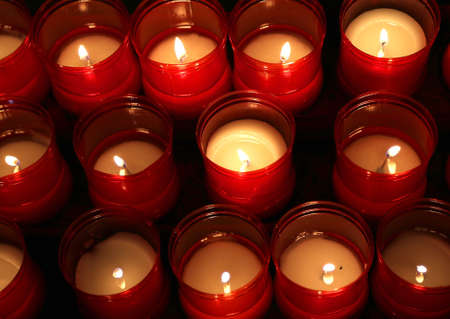 series of candles lit inside the church to pray Stock Photo