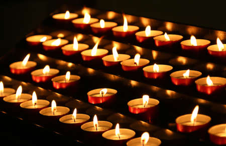 many candles lit with flickering flame in the sanctuary
